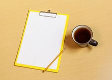 Clipboard with white sheet, cup of tea and pencil Royalty Free Stock Photo