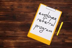 Clipboard with white sheet on wood background. Employee referral program stock image