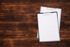 Clipboard with white sheet on wood background. Top view stock photo