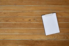 Clipboard with white sheet on wooden background stock photo