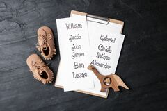 Free Clipboard With List Of Baby Names, Child`s Shoes And Wooden Toy On Black Table, Flat Lay Stock Photography - 203872062