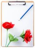 Clipboarden med ron och ritar på pappers- vit Arkivbilder