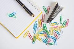 Clipe de papel e caderno com a pena no fundo branco Imagens de Stock Royalty Free