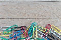 Clipes de papel coloridos no fundo de madeira com espaço da cópia imagens de stock