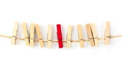 Clipes de papel de madeira da cor natural com vermelho um no meio Imagens de Stock