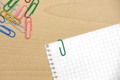 Clipes de papel na madeira com papéis da grade Foto de Stock