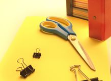 Clipes de papel, tesouras e papel na tabela na perspectiva de um dobrador e etiquetas para notas foto de stock
