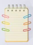 Clipes e livro de nota coloridos no fundo branco isolado Fotografia de Stock