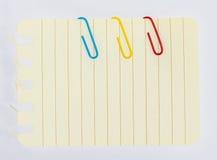 Clipes e livro de nota coloridos no fundo branco isolado Imagem de Stock Royalty Free