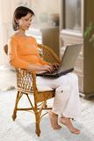 CLIPPING PATH! Woman with laptop on the chair. Contains Clipping Path. Get rid of background with single click Royalty Free Stock Images