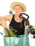 Clippings Gardener. Middle aged gardener with grass cutter puts his garden clippings into a rubbish bag Stock Photo