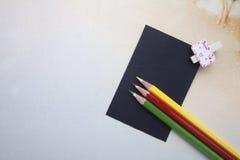 Clips de madera, notas pegajosas y lápices del color Foto de archivo libre de regalías