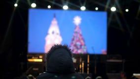 Clips de observación de la gente de la celebración próxima en la pantalla grande en cuadrado central almacen de video