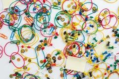 Clips de papel coloridos, tachuelas de pulgar de los pernos de dibujo, caucho elástico Fotos de archivo libres de regalías