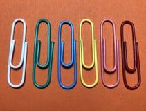 Clips de papel consecutivos coloridos en fondo anaranjado Foto de archivo
