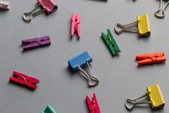 Clips de papel y pinzas de Multiculored en fondo gris imágenes de archivo libres de regalías