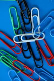 Clips on different color. On the blue background Royalty Free Stock Photos