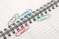 Clips scattered on a notebook Royalty Free Stock Photo