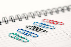 Clips scattered on a notebook Royalty Free Stock Image