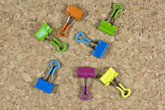 Clips of various colors and the background of cork. Stationery in a mess on the table Royalty Free Stock Photos
