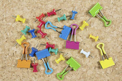 Clips of various colors and the background of cork. Stationery in a mess on the table Royalty Free Stock Images