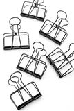 Black Clips on white background. Clips on white background shot in studio Stock Images