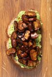 Wholewheat toast on sutting board. Clise up of wholewheat toast with mashed avocado and grilled mushrooms on a cutting board royalty free stock photography