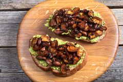 Wholewheat toast on sutting board. Clise up of wholewheat toast with mashed avocado and grilled mushrooms on a cutting board royalty free stock photo