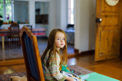 CLittle-Mädchen, das auf Stuhl im Wohnzimmer sitzt stockbilder