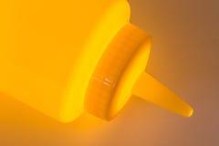 Clloseup di plastica giallo della bottiglia della senape con una luce d'ardore Fotografia Stock Libera da Diritti