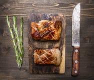 Δύο εύγευστο ψημένο στη σχάρα κομμάτι του χοιρινού κρέατος σε έναν πίνακα κοπής με ένα μαχαίρι για τοπ άποψη clo υποβάθρου κρέατο Στοκ Εικόνες