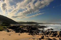 海滩前的黑色晃动Cloady天空 免版税库存图片