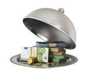 Cloche argentée de restaurant avec des billets de banque et des pièces de monnaie Photo stock