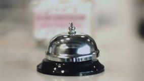Cloche argentée de sonnerie de service de main humaine sur la réception d'hôtel clips vidéos