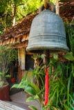 Cloche de fer avec la maison en bambou locale Image libre de droits