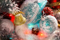Cloche de Noël d'or accrochant sur une branche avec des décorations de Noël lumières multicolores, rayonnement, tresse brillante Photographie stock