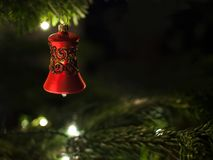 Cloche rouge décorative avec les ornements brillants accrochant sur l'arbre de Noël avec des lumières à l'arrière-plan image libre de droits