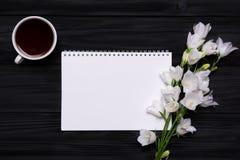Cloches de fleurs blanches, café et carnet vide pour votre texte sur le noir Photos libres de droits