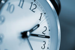 Clock. With selective lighting and blue hue.  Focus on number one Stock Photo