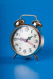 Clock. Golden alarm clock isolated on blue background Stock Images