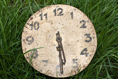 Clock. Very old clock in the green grass Royalty Free Stock Photography