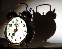 Clock. With its shadow in background stock photography