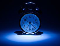 Clock. Alarm clock on blue dark background stock images