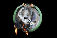 Clock. In fire on black background Royalty Free Stock Photos