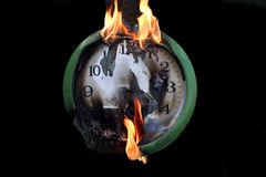 Clock. In fire on black background Stock Photos