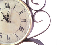 Clock. Close up of a clock face with wrought iron accents over white royalty free stock image