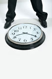 Clock. Businessman legs standing next to a big clock Royalty Free Stock Photography