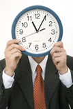 Clock. Businessman holding a clock in front of his face Royalty Free Stock Photo