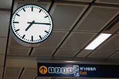 Clock in airport with signboard Stock Photography