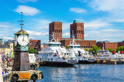 Clock on Aker Brygge, modern and Oslo City Hall royalty free stock photo